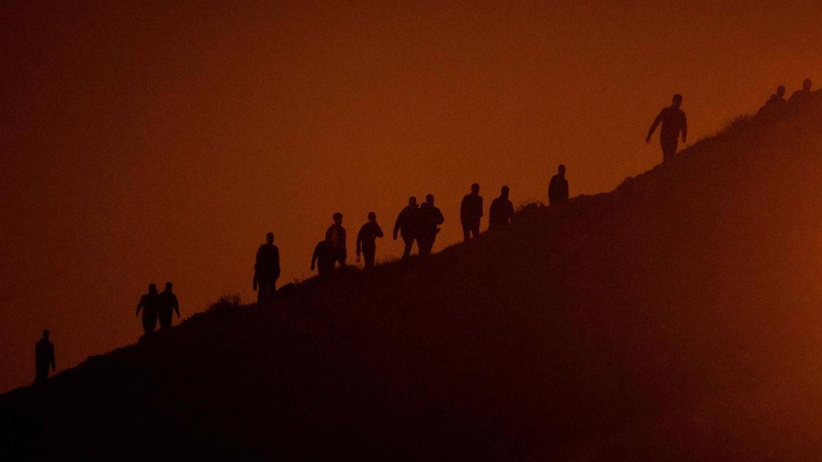 Migrantes caminan por un acantilado en Fnideq, con la intención de cruzar a España desde Ceuta.