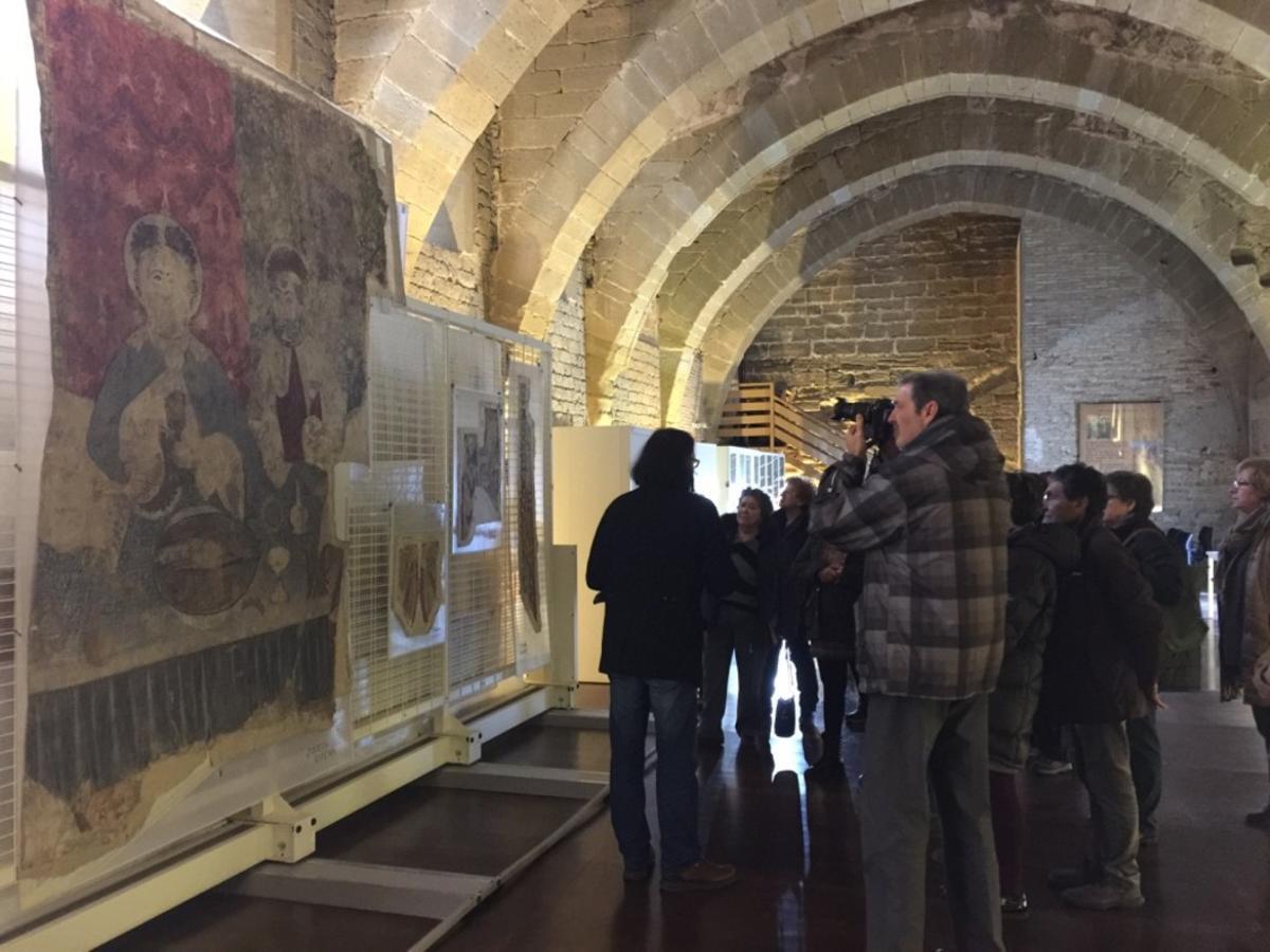 Los visitantes frente a las cuatro pinturas que se pueden ver, detrás se aprecian los peines con el resto de murales.