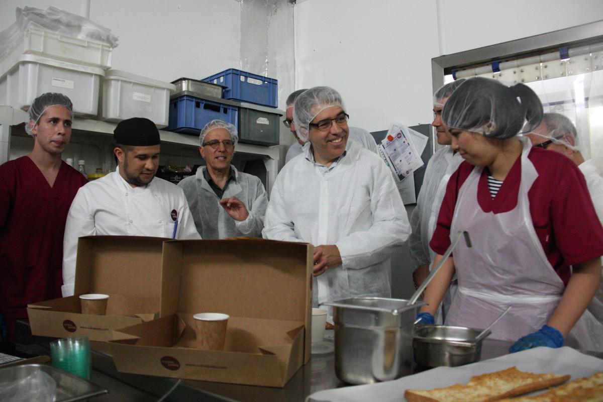 Francesc Homs, candidato de CDC, con trabajadores de la Fundació Cuina Justa-Cassià Just, en Sant Boi de Llobregat.