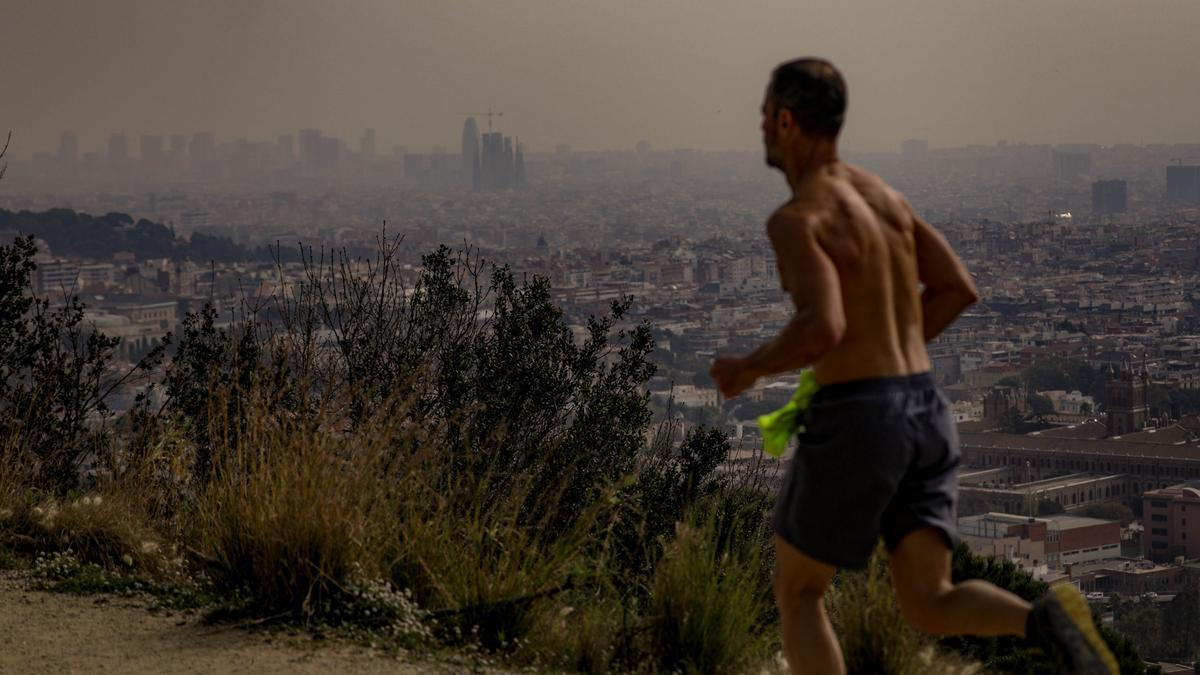 Un corredor en la carretera de las Aigües, con la calima sobre el cielo de Barcelona, este viernes