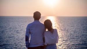Una pareja contempla el mar de espaldas.