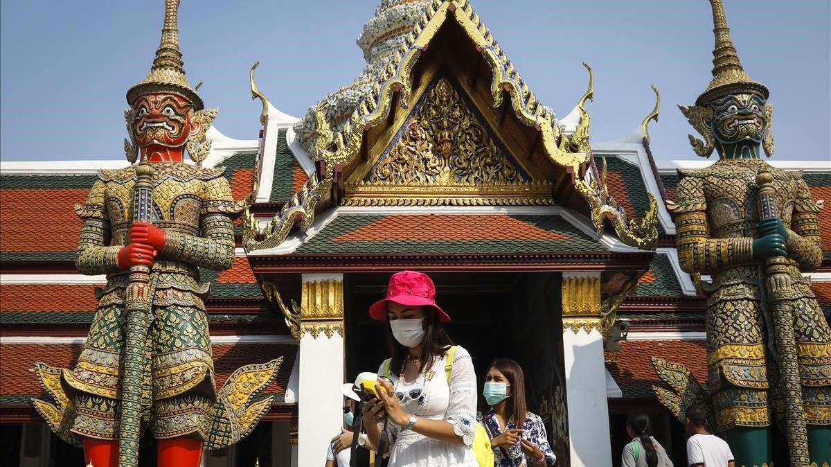 Turistas con mascaras junto al Palacio Real de Bangkok, este sábado.