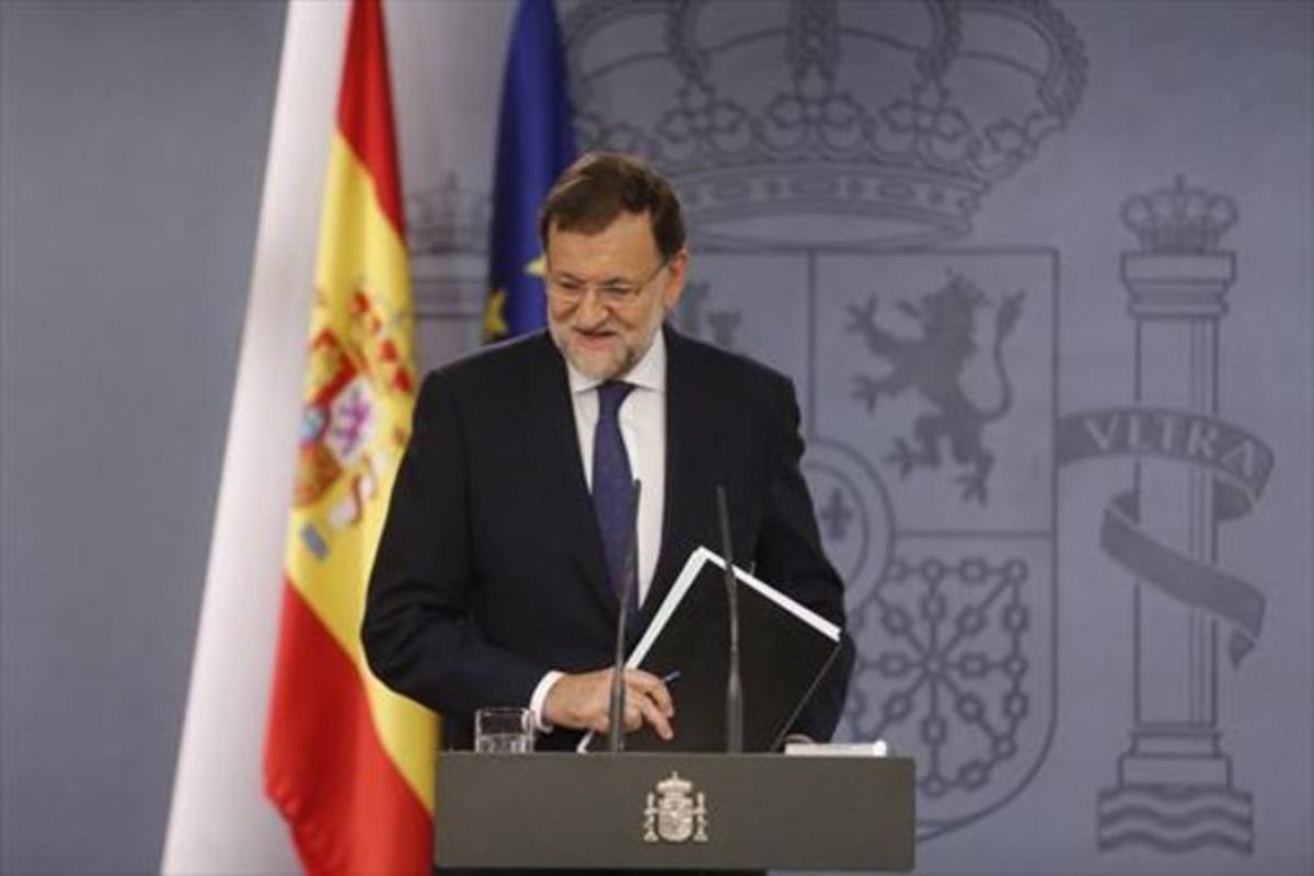 Rajoy recoge sus papeles tras la comparecencia en la Moncloa.