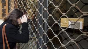 Una mujer mira a través de un establecimiento cerrado.