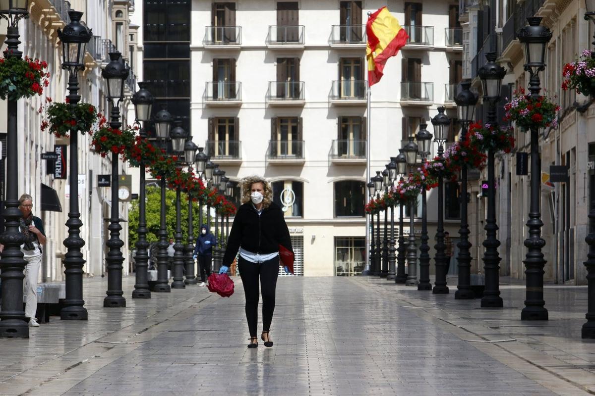 Una mujer con mascarilla recorre la calle Larios durante el segundo día laborable del estado de alarma a causa de la pandemia del nuevo coronavirus (COVID-19). En Málaga, (Andalucía, España), a 17 de marzo de 2020.