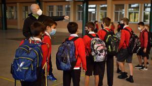 Un grupo de jóvenes estudiantes con mascarilla protectora para prevenir la propagación del coronavirus se desinfectan las manos antes de ingresar a la escuela Luis Amigo, en Pamplona.