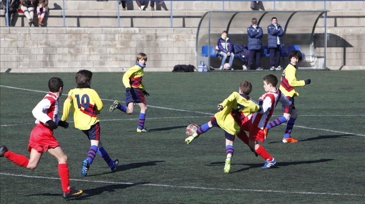 Niños jugando a fútbol en el campo del CF Alzamora, en el barrio de Porta de Barcelona.