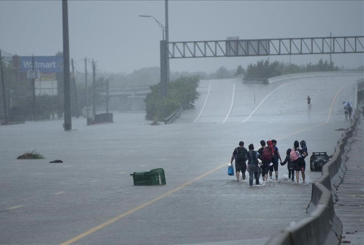 Un grupo de personas avanza por una avenida de Houston cubierta de agua.