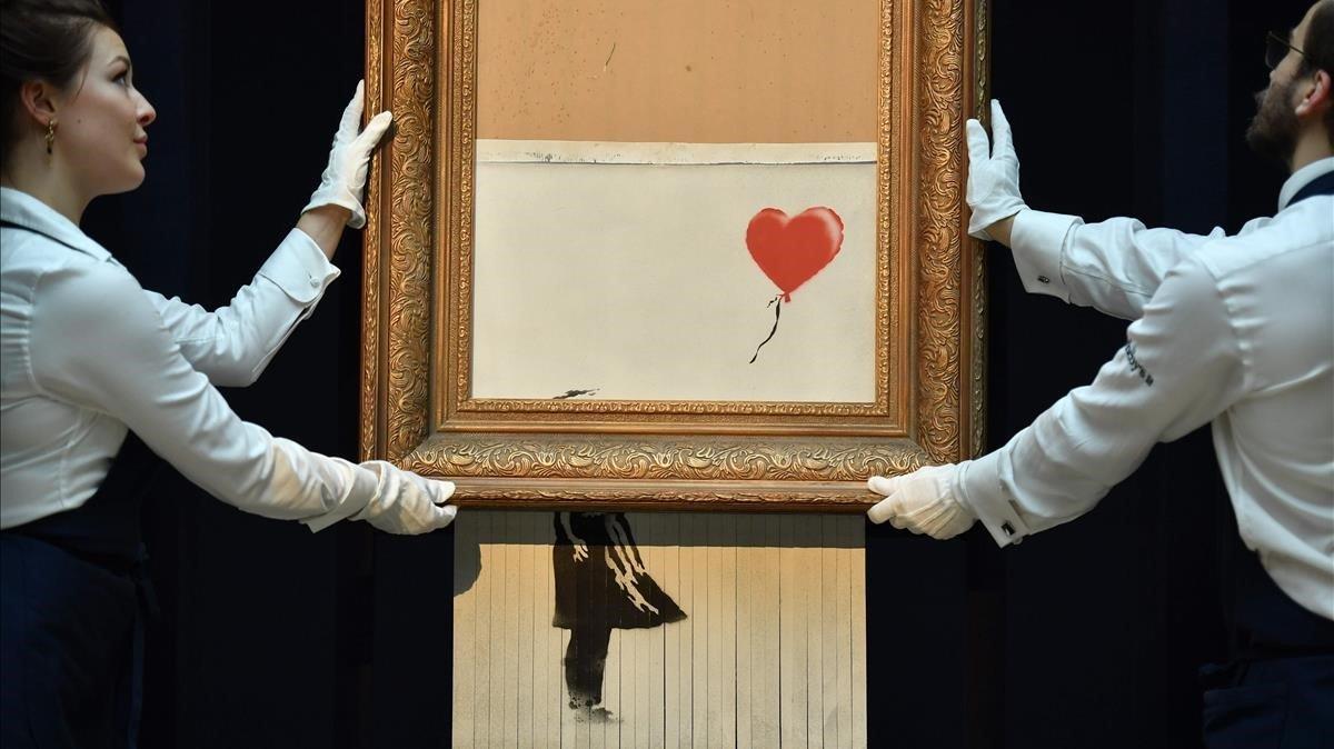 Empleados de Sotheby's muestran'Love is in the bin' de Banksy, la nueva pieza resultado de la autodestrucción, en plena subasta, de 'Girl with a balloon'.