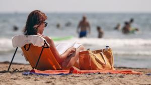 una mujer lee un libro este mediodía en la playa.