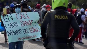 Una manifestante muestra un cartel a un policia durante una de las protestas del martes pasado en el barrio Siloe de la localidad colombiana de Cali.