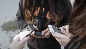 Tres chicas muestran sus teléfonos móviles.