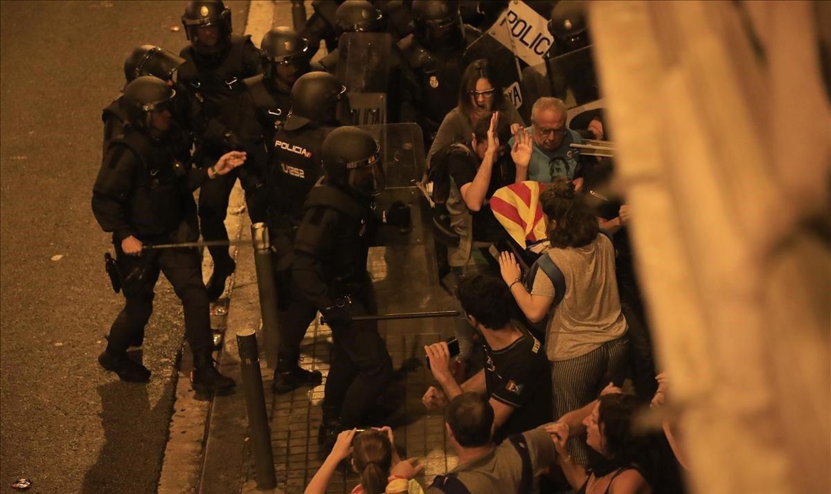 Los antidisturbios de los Mossoss d'Esquadra contienen a manifestantes en la Vía Laietana de Barcelona, junto a la comisaría de la Policía Nacional.