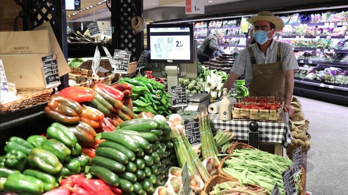 Un empleado de un supermercado de Madrid se protege con mascarilla y guantes.