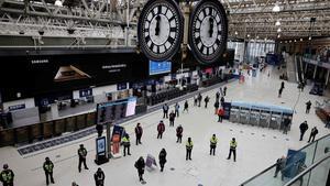 Viajeros y trabajadores participan en un minuto de silencio en el primer aniversario del cierre nacional por covid-19 en la estación de Waterloo, en el centro de Londres.