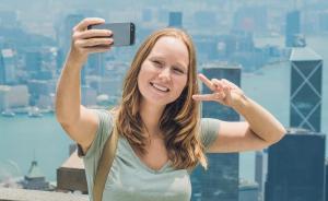 Una chica se hace un selfi haciendo el sígno de victoria.