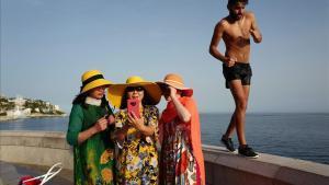 Un hombre pasa junto a unas turistas que se hacen una foto en Niza, Francia.