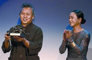 Kim Ki-duk, ayer en Venecia, en el momento de recibir el León de Oro acompañado de la actriz coreana Jo Min.