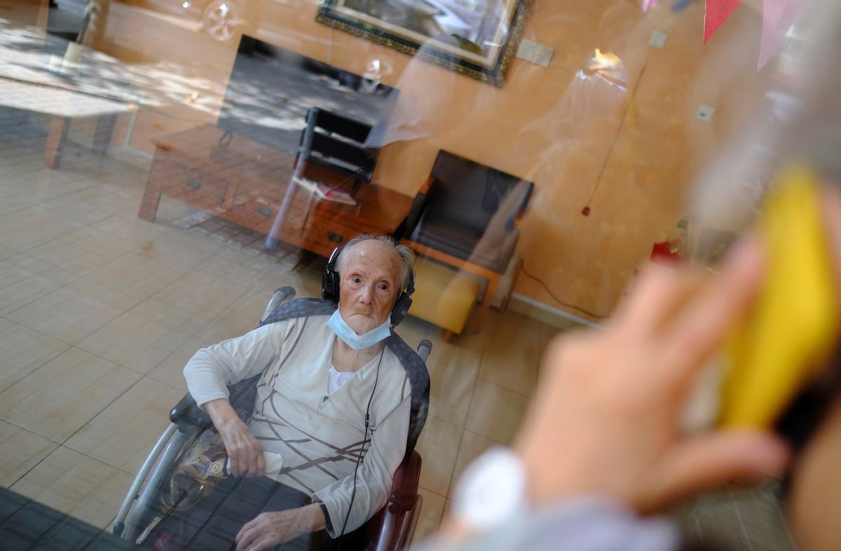 Una anciana escucha a su hija a través de una mampara en una residencia de Barcelona.