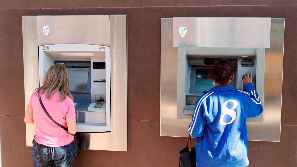 Dos personas sacan dinero de sendos cajeros automáticos en Madrid.