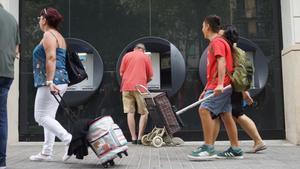 Una persona mayor saca dinero de un cajero en Barcelona.