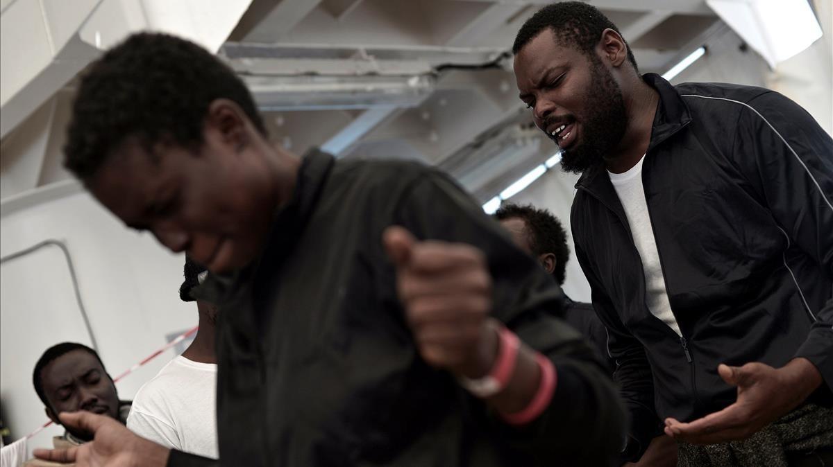 Refugiados recogidos por el 'Aquarius', rezando a bordo del barco humanitario.