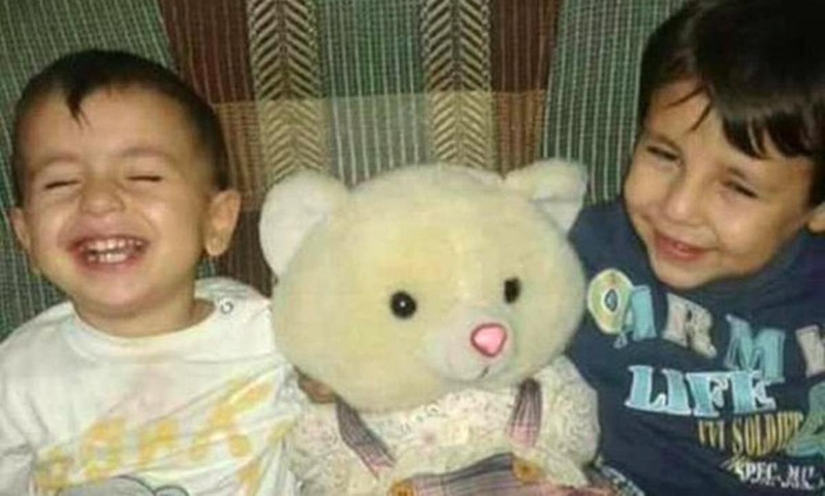 El niño sirio Aylan, de 3 años, y su hermano mayor Galip, de 5, ríen mientras juegan con un osito de peluche.