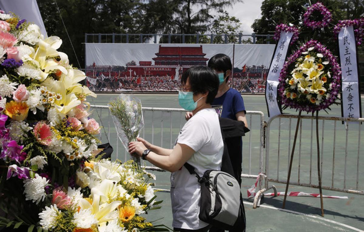 Dos mujeres colocan flores en el memorial a las víctimas de Tiananmen, en Hong Kong.