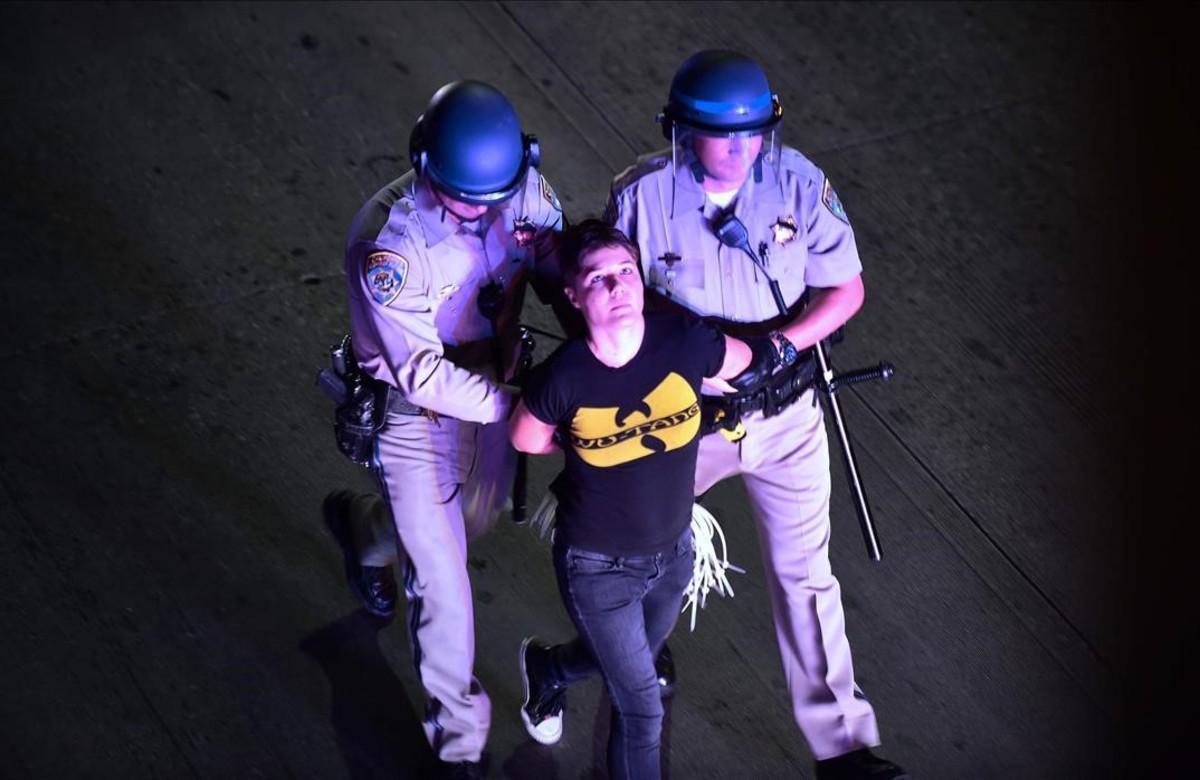 Una joven es detenida durante los distubios en Los Angeles.