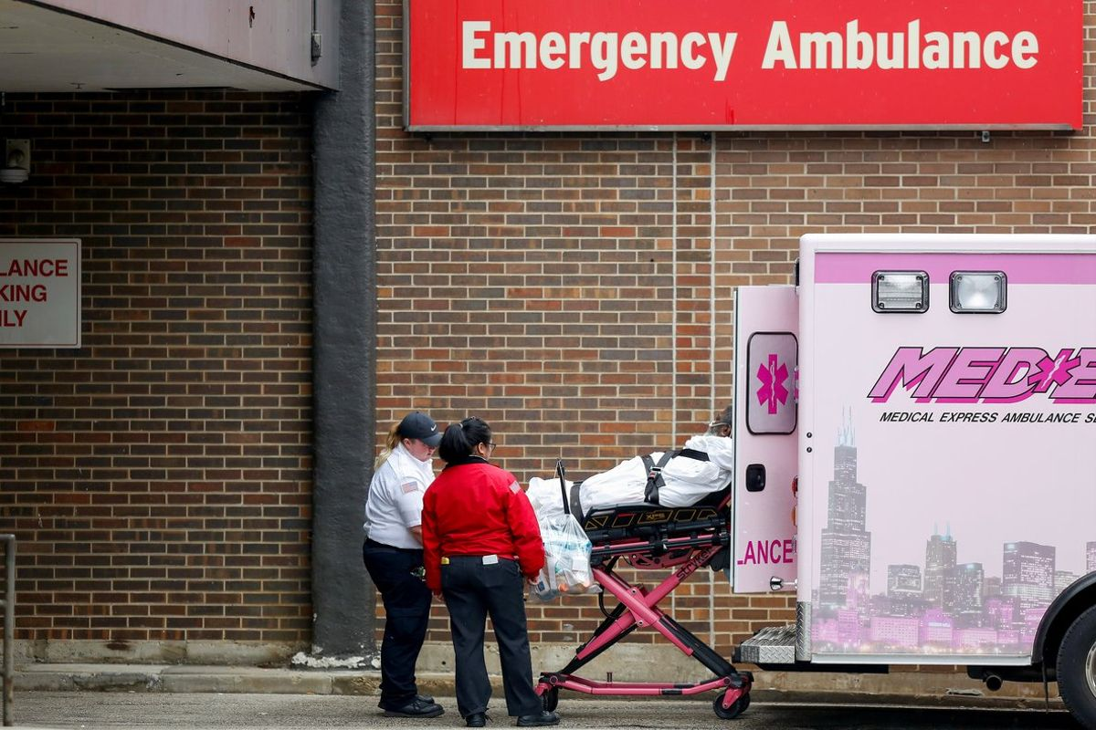 Emergency medical service workers place a patient into an ambulance outside the University of Illinois Hospital as the Illinois Nurses Association reports 12 registered nurses tested positive for the coronavirus disease (COVID-19), in Chicago, Illinois, U.S. March 27, 2020. REUTERS/Joshua Lott