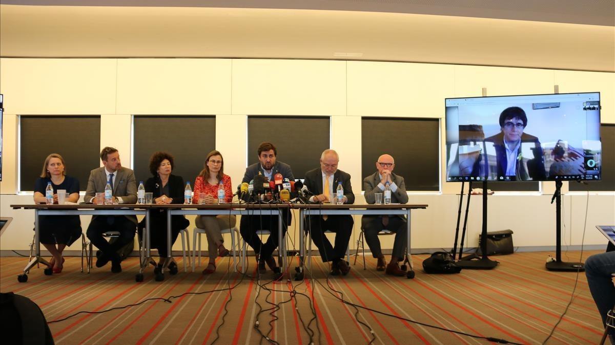 Toni Comín, Meritxell Serret y Lluís Puig junto a los abogados belgas del equipo de defensa y Carles Puigdemont a la pantalla durante la rueda de prensa de hoy en Bruselas
