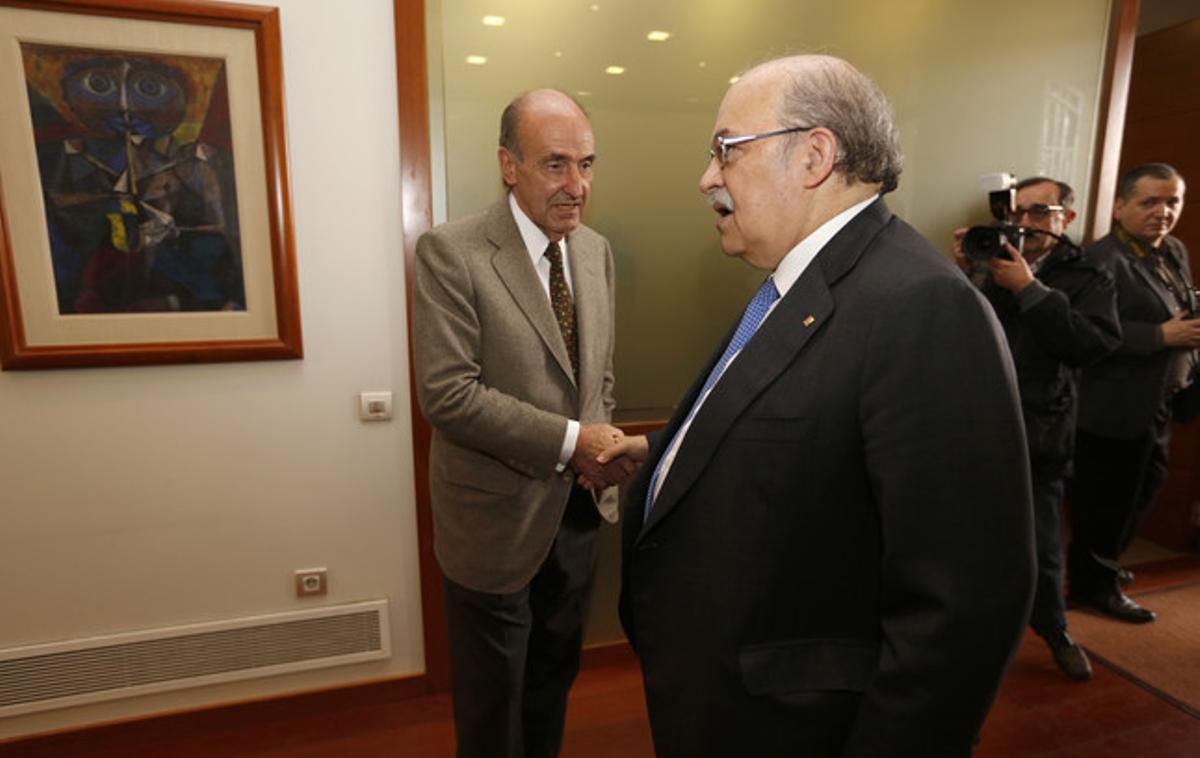 Andreu Mas-Colell (derecha) saluda a Miquel Roca, el miércoles en Barcelona.