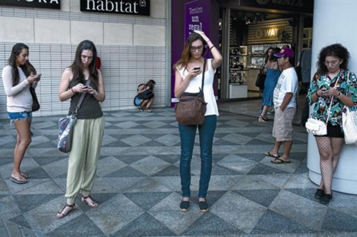 Cuatro ciudadanas consultan sus 'smartphones' en la plaza de Catalunya, en Barcelona.