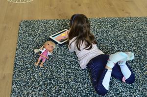 Una niña se entretiene en casa con una tablet y muñecas.