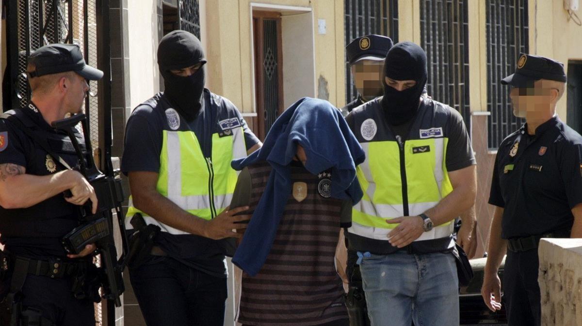 Efectivos de la Policia Nacional traslada a una persona detenida durante el registro realizado hoy en un domicilio del barrio periferico del Monte Maria Cristina de Melilla en el marco de una operacion antiterrorista que se esta llevando a cabo en Melilla en la que tambien se ha producido un registro en la calle de Garcia Cabrelles La Policia Nacional y la Direccion General de Seguridad de Marruecos han desmantelado una celula yihadista integrada por seis presuntos terroristas en una operacion en la que han sido detenidas cinco personas en Marruecos y otra en Melilla