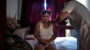 Una mujer recibe en su casa la primera dosis de la vacuna de Coronavac contra la covid-19, en Sao Leopoldo (Brasil).