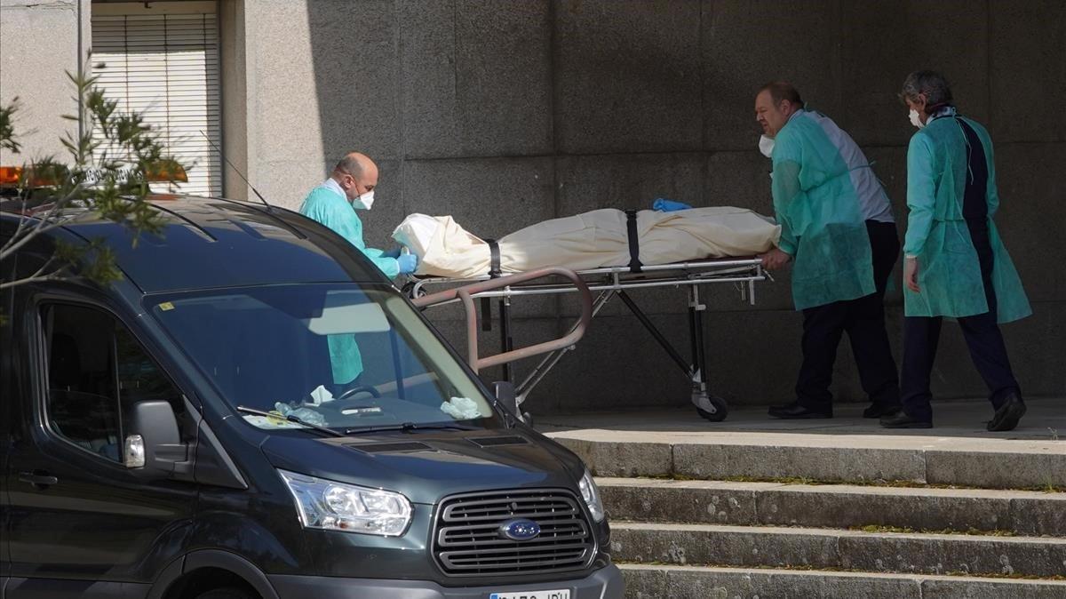 Operarios de los servicios funerarios sacan este miércoles uno de los cadáveres de la residencia de mayores Doctor González Bueno de Madrid.