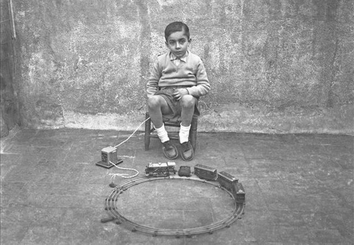 Un niño posa con su tren eléctrico en mitad de una habitación desoladora.