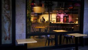 Un camarero tras la barra del restaurante ya cerrado por el toque de queda