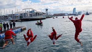 Varios participantes disfrazados de Papa Noel se lanzan al agua para participar en la Copa Nadal
