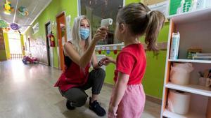 Olimpia Selva, que regenta el centro de educación infantil 'Mi pequeña escuela', en la pedanía murciana de La Alberca, toma la temperatura a una niña antes de entrar en la guardería.