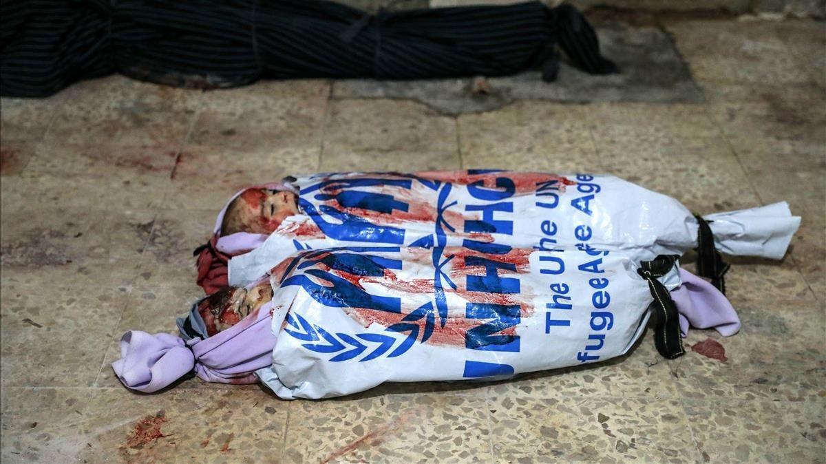 Los cadáveres de dos niños muertos por los bombardeos en Duma yacenenvueltoscon ropa del ACNUR, la oficina de la ONU para los refugiados.