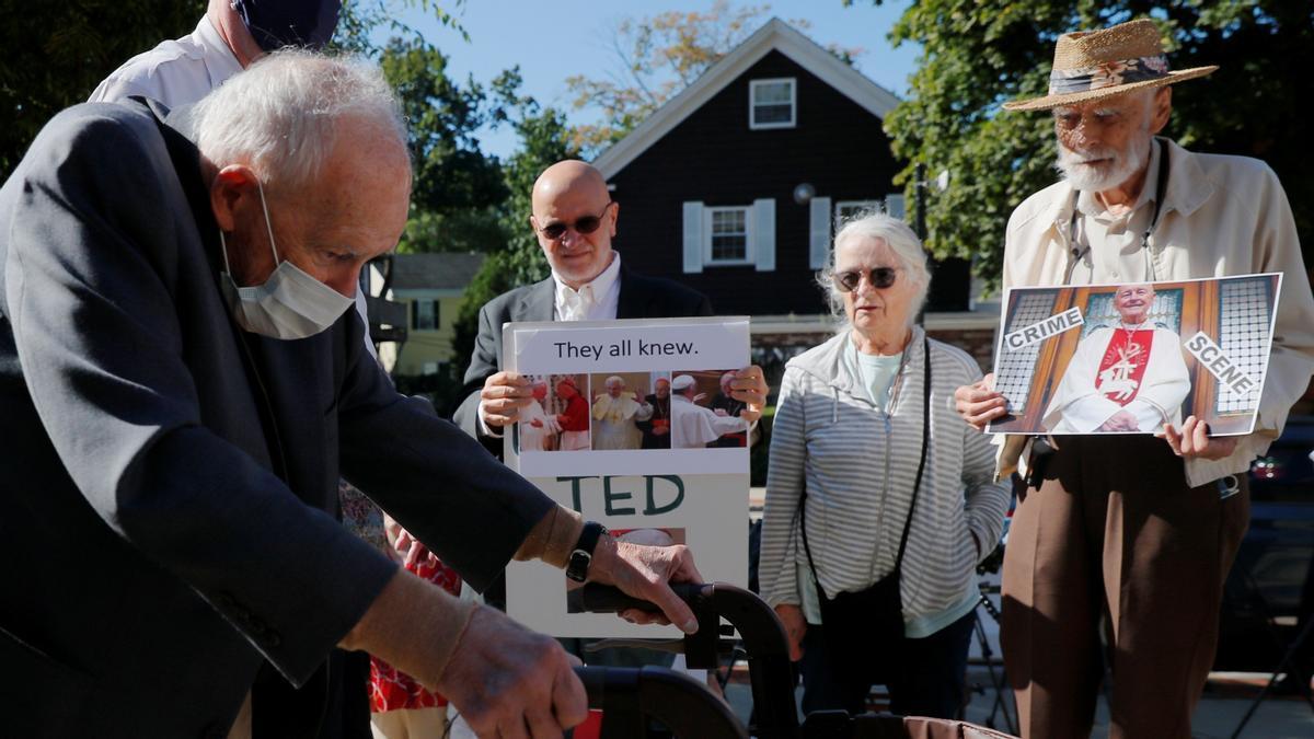 El excardenal Theodore McCarrick pasa por delante de protestantes que se han congregado en las puertas de la Corte de Distrito de Dedham (Boston) en su vista, este viernes.
