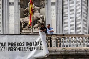 Dos trabajadores de la Generalitat retiran la pancarta que colgaba del Palau, el pasado 27 de septiembre.