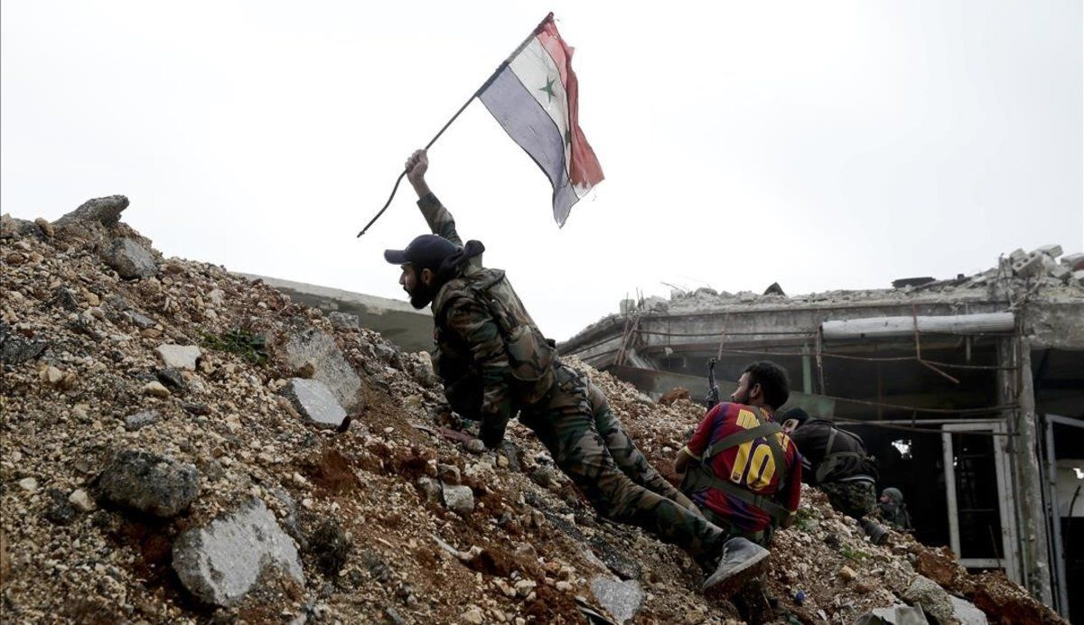 Un soldado del Ejército sirio coloca una bandera nacional durante una batalla con combatientes rebeldes en Alepo.