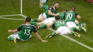 Los jugadores de Irlanda del Norte celebran el primer gol en el mojadísimo terreno de juego de Lyón