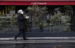 Un parisino camina frente a un café cerrado debido a las restricciones por el coronavirus