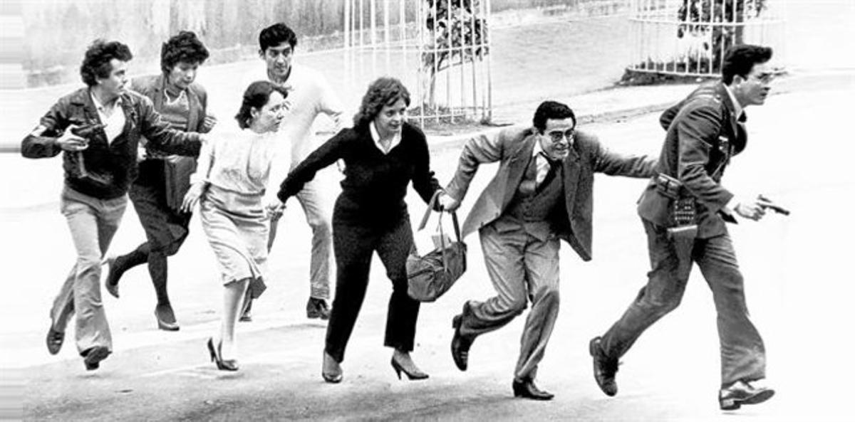 EVACUADOS Empleados del Palacio de Justicia abandonan el edificio por una calle lateral  acompañados por personal de la policía, el 6 de agosto de 1985, después de que el lugar fuera tomado por el M-19.