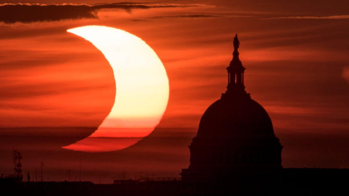 Así se ha visto el primer eclipse solar anular del 2021. En la foto, el eclipse visto sobre el capitolio de Washington, en una imagen tomada desde Arlington, Virginia.