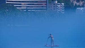 Un hombre practica padel surf en la playa de la Malagueta (Málaga) en medio de la niebla, el pasado día 19.